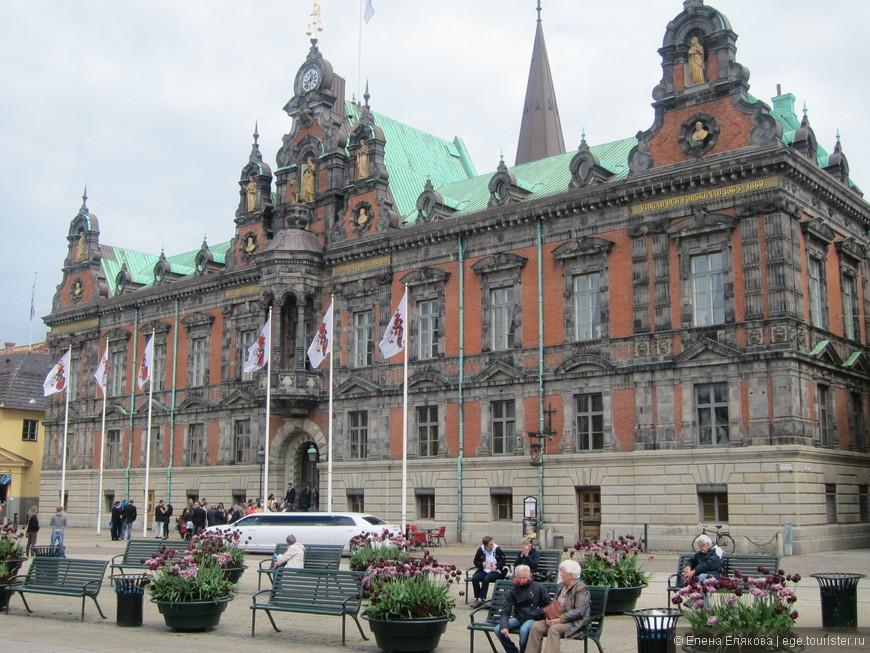 Большая площадь (Stortorget). Видимо, это мэрия или другое административное здание, так как намечается регистрация свадьб, белый лимузин - свадебный.