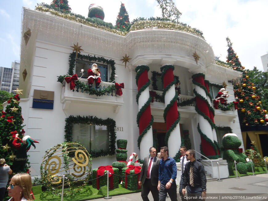 Деды Морозы на здании поют рождественские песни