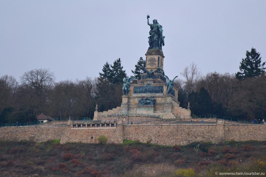 Памятник объединению Германии в Нидервальде.Памятник, общая высота которого составляет 38 м, был заложен в 1877 году в присутствии первого кайзера объединенной Германии Вильгельма I в память об образовании Германской империи в 1871 году. В гордо поднятой правой руке Германия держит императорскую корону, в левой – так называемый имперский меч, одну из немецких государственных регалий, символизируя воссоздание средневековой германской империи. После открытия памятник был объявлен одним из величайших произведений искусства своего времени. На открытии памятника в 1883 году лично присутствовали германский кайзер Вильгельм I, а также все немецкие князья. Даты и гербы на цоколе памятника напоминают о создании Германской империи в 1871 г. Желающие подняться к памятнику могут воспользоваться фуникулером, который провезет их через виноградники прямо к фигуре Германии. Из-за сильного ветра фуникулёр закрыли.