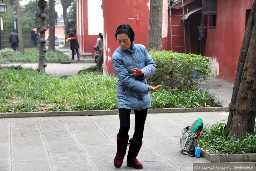 бодрая китайская бабушка, одна, отрабатывает практики тайцзи, Монастырь Манджушри, Чэнду