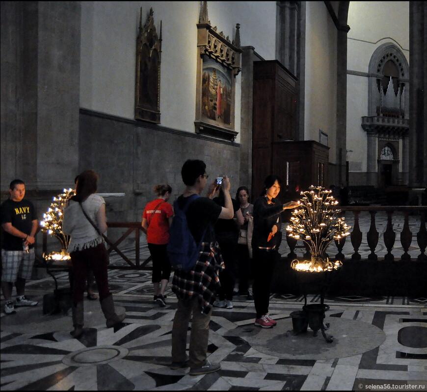 У подсвечника-дерева  туристы возжигают  восковые свечи. Во многих храмах Италии используются  вместо свечей  электрические лампочки.