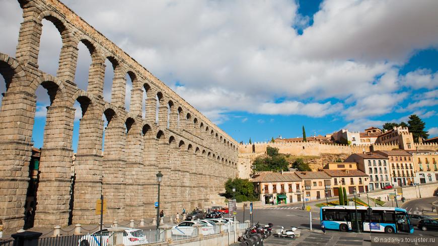 """Акведук """"стыкуется"""" к крепостным стенам старого города. Внизу начинают прибывать туристические группы. На удивиление, в инфоцентре даже встретился русский мальчик. Что была большая редкость в этом регионе Испании."""