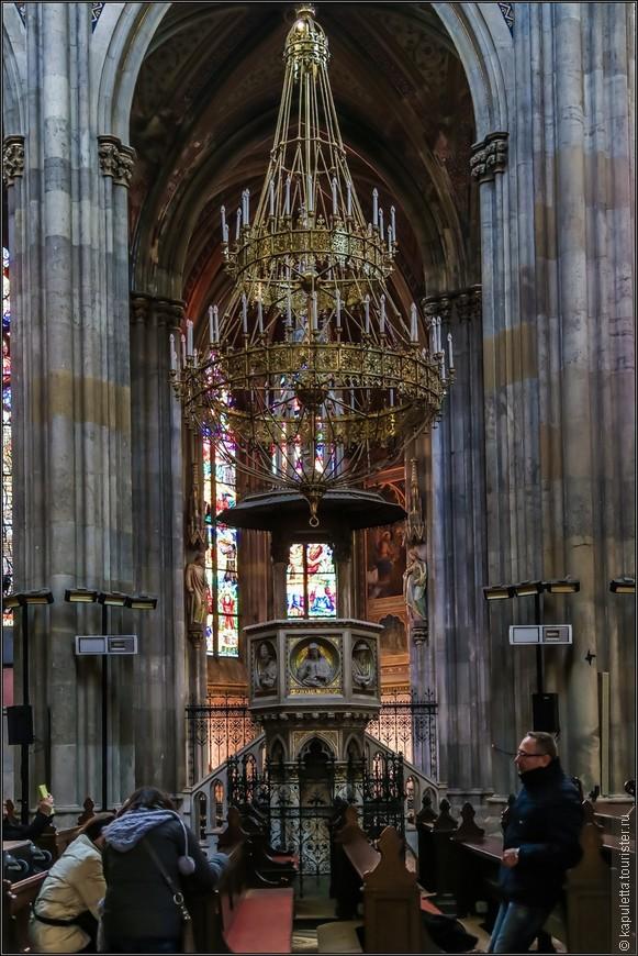 Шестиугольная неоготическая кафедра стоит на шести мраморных столбах. Передние панели изображают посередине молящегося Христа, окруженного по обеим сторонам отцами церкви: Св. Августином, Св. Юрием, Св. Иеронимом и Св. Амвросием. Эти полурельефы заключены в углубленные медальоны с позолоченным мозаичным фоном. Четыре колонны поддерживают деревянную резонансную доску и шпиль со статуей Иоанна Крестителя. И так, как скульптор Собора Св. Стефана был изображен под кафедрой, так и архитектор Вотивкирхе, Генрих Ферстель, изображен Виктором Тильгнером под этой кафедрой.