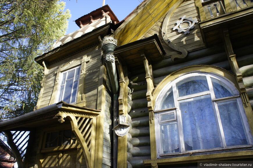 Характерны округлые окна, навес над входом, резьба на водосточной трубе и выход на балкон в мансарде.