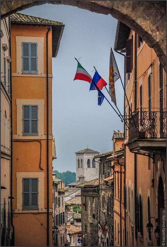Изначально у города было латинское название - Assisium, в давние времена он был известен как место, где родился римский поэт Секст Проперций.