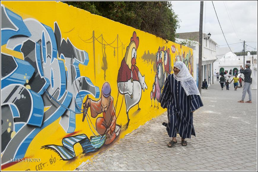 Первое, что мне пришло в голову, когда мы увидели работы художников, а как на это реагируют местные жители? Вот эта бабуля явно довольна, что не надо будет красить заборы.