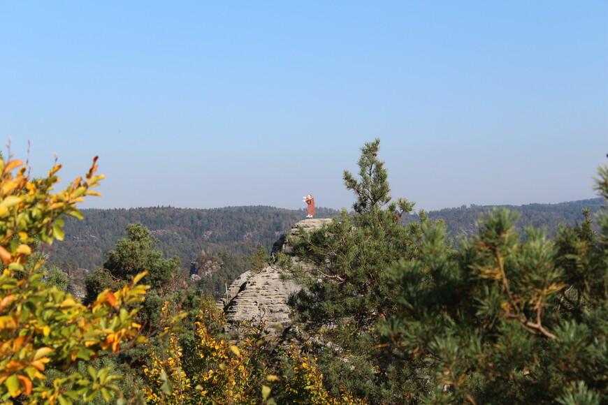 На вершине одного каменного столба стоит деревянная фигура человека – это скульптура святого, покровителя Ратена и его жителей.