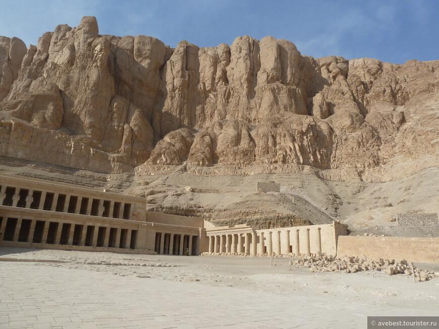 Этот путь, шириною около 37 метров, с обеих сторон охранялся сфинксами, выполненными из песчаника и раскрашенными яркими красками. Прямо перед храмом были разбит сад диковинных деревьев и кустарников, привезенных из загадочной страны Пунт. Здесь же были вырыты два священных озера Т-образной формы. Сам храм был поистине чудом инженерной мысли древних египтян. Вырубленный в известняковых скалах, он состоял из трех огромных террас, расположенных одна над другой. На каждой из террас находились открытый двор, крытые помещения с колоннами - портики - и уходившие в толщу скалы святилища. Ярусы храма соединялись пандусами - наклонными дорогами, заменявшими лестницы и разбивавшими террасы на южную и северную части.