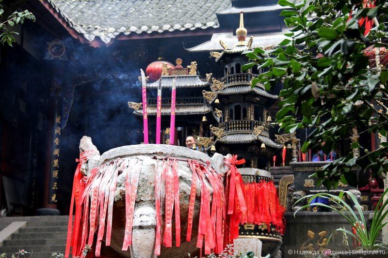 курильницы во дворе храма, красные ленточки - просьбы о продолжении рода и о прочих благах
