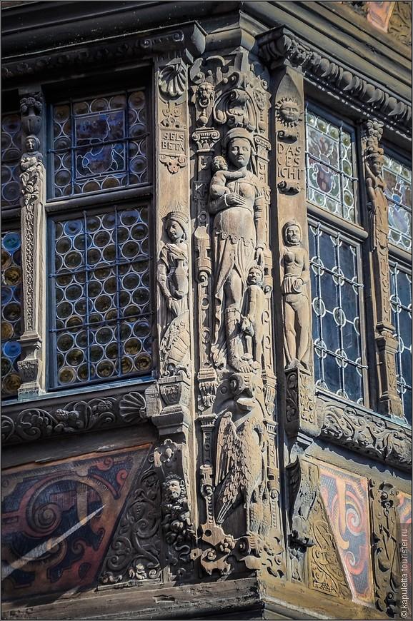 Мало того что он чрезвычайно богато украшен деревянной скульптурой, так еще имеет целых 75 окон, что также можно считать излишеством для относительно небольшого жилого строения. Каждое из 75 окон имеет пышное обрамление в виде фигур, изображающих пятнадцать музыкантов, двенадцать знаков Зодиака, различных библейских и мифических героев, героев античности и символы пяти чувств. На угловой опоре вырезаны три высокие женские фигуры, воплощающие христианские добродетели. На втором этаже изображена Любовь с двумя детьми (одного она держит на руках, а другому протягивает руку) и пеликаном. Пеликан — частый атрибут аллегорического изображения любви. Он символизирует родительскую любовь, самопожертвование и самоотречение. Это одна из наиболее известных аллегорий Христа, спасшего человечество своей кровью (согласно легенде, пеликан разрывает клювом собственную грудь и кормит голодных птенцов кровью). Данте в «Божественной комедии» называет Христа «пеликаном человечества». Пеликан у ног женской фигуры, олицетворяющей Любовь.
