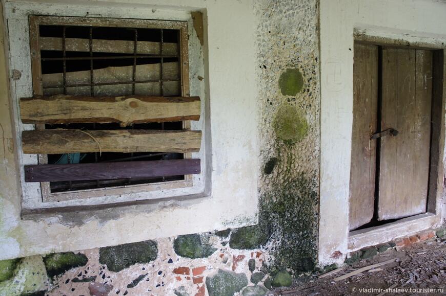 Окно заколочено, дверь закрыта на замок. Но на этой стене видно многообразие кладки.