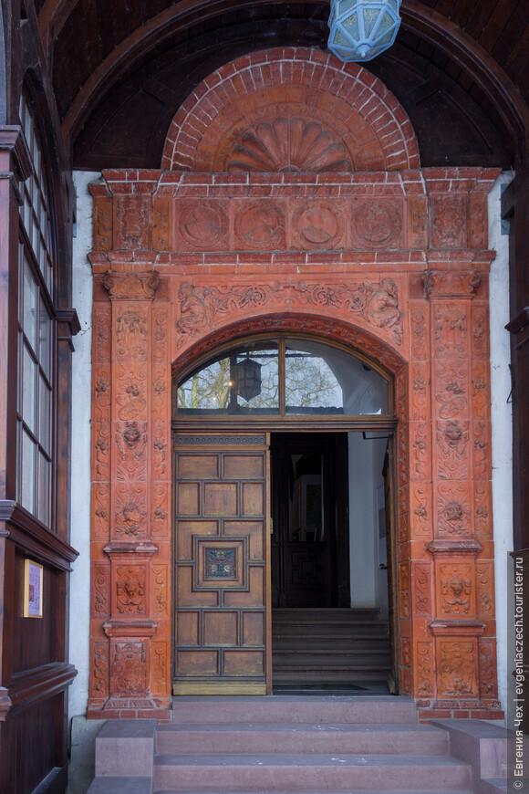 Дубовые двери с геральдической символикой украшены терракотовыми плитками в стиле 16 века.