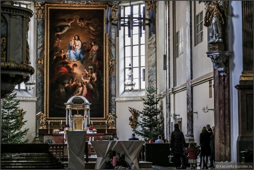 """На восточном краю площади Ам-Хоф, на месте придворной романской капеллы, в 1403 году кармелиты построили трёхнефный костёл «Девяти ангельских хоров"""".  Название связано с тем, что в оформлении алтаря присутствует Дева Мария, окруженная девятью ангельскими хорами. Реформация привела церковь к упадку, и Фердинанд I отдал её в 1554 г. ордену воинствующих иезуитов."""