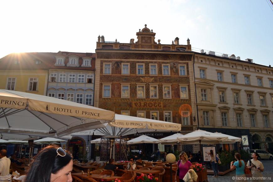 """Роттов дом (№3) (dům U Rotta). Это был первый в Праге каменный дом. В течение нескольких веков он сменил немало владельцев, пока его не приобрел Ротт, о чем свидетельствует надпись """"V.J.Rott"""". Дом был перестроен в новоренессансном стиле в 1890 году. Удивительно красивые фрески на фасаде, аллегории земледелия и ремесел в красно-бордовых тонах по картонам Миколаша Алеша были рекламой магазина, который находился в здании. А в XV веке здесь находилась типография печатника Пытлика, в которой появилась на свет первая чешская Библия"""