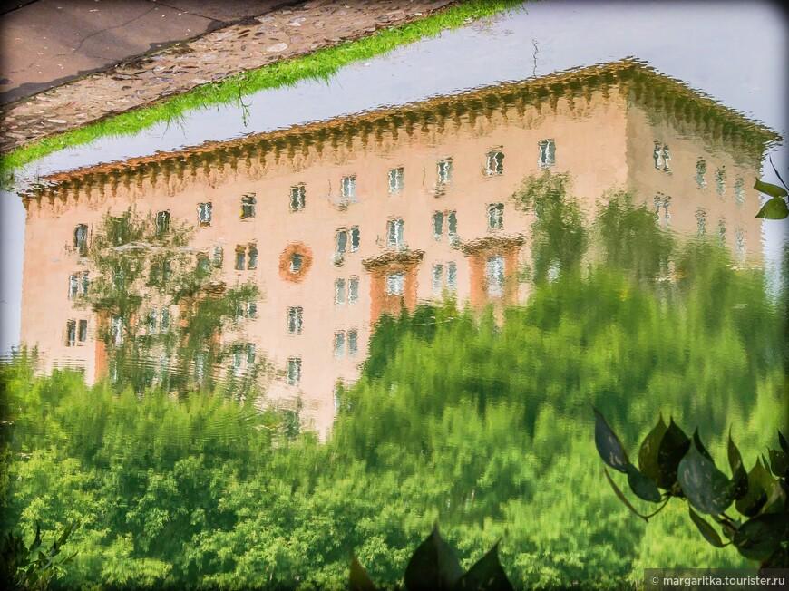 отражение в монастырском пруда сталинского дома по соседству с монастырем