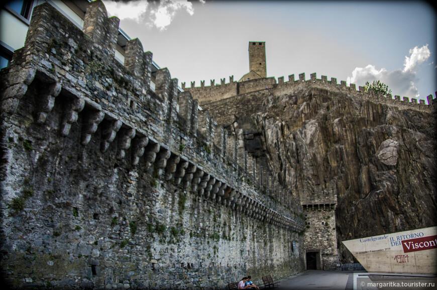 Над старым городом, возведенном в ломбардском стиле, возвышается замок Кастелгранде (12-13 век, расположен на западном холме, ныне занят тюрьмой и арсеналом кантона). Замок Кастельгранде располагается в историческом центре города, в 500 метрах к юго-западу от вокзала, рядом с центральной площадью piazza Collegiata и кафедральным собором святых Петра и Стефана. Замок стоит на скалистой возвышенности, имеющей почти отвесные склоны с северной стороны, крутой подъём с юга и почти плоскую вершину, 150 – 200 метров в диаметре.