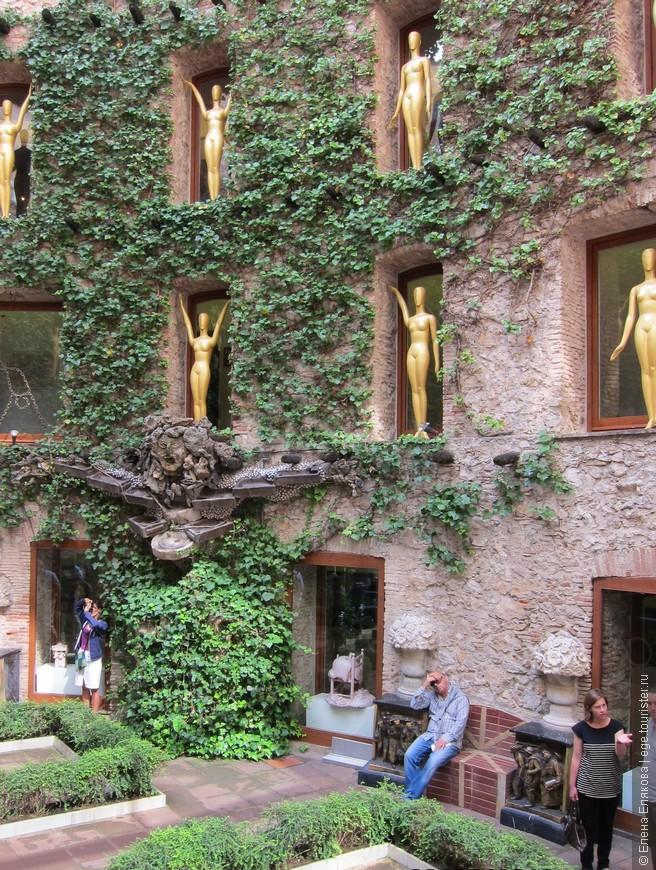 Двор театра-музея.  Золотые манекены в стиле арт-деко приветствуют посетителей.