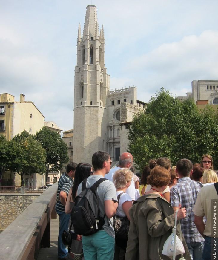 На заднем плане - церковь Святого Фелиу - Esglesia De Sant Feliu. В её часовне хранятся мощи Святого Нарцисса, особо почитаемого Святого в Жироне. Во время очередной осады французской армией, разъяренные невозможностью захватить город, и зная о почитании жиронцами Святого Нарцисса, французы решили осквернить могилу, в которой покоились его останки. Когда же солдаты приподняли крышку гроба, из саркофага вылетел рой необычных зелёных мух, размером с жёлудь и большим жалом. Они набросились на захватчиков и их лошадей. Началась паника, и французы отступили. Укусы мух были смертельны. Более двадцати тысяч человек, включая самого короля, погибли по дороге домой, во Францию. С тех  пор символом города является муха.