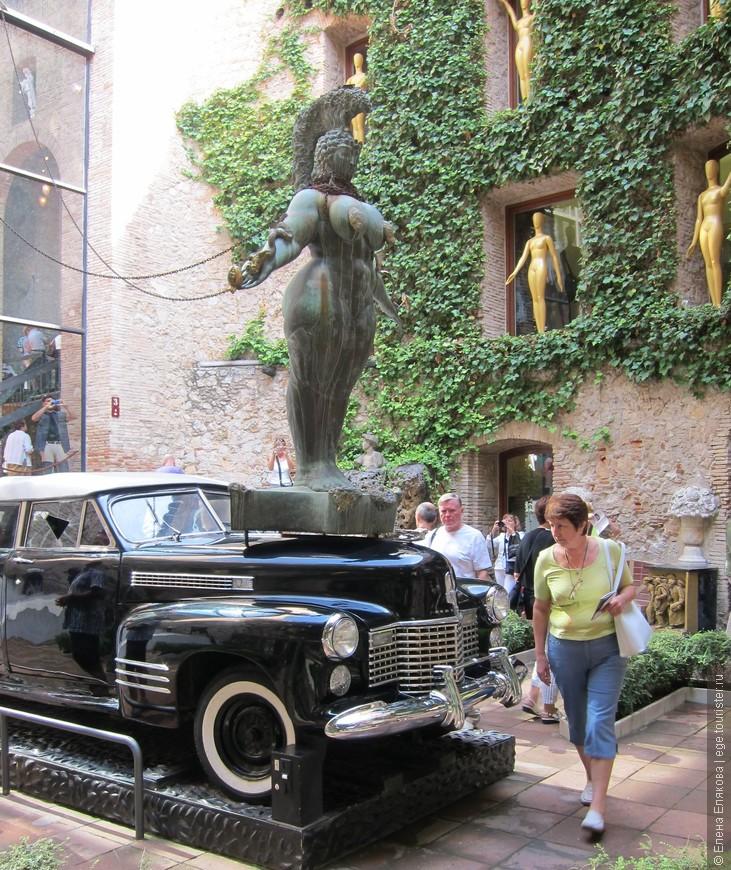 """Двор театра-музея. """"Дождливое такси"""" - Дали создал его к Всемирной выставке сюрреализма в Париже (1938 г.), в нем идет дождь, если опустить монетку. В машине сидят 3 манекена - водитель и 2 пассажира, обвитые плющом."""
