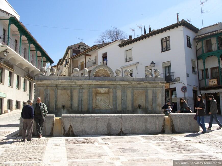 Большой каменный фонтан, на котором изображён большой каменный герб города. Из пары труб течет чистая питьевая вода   Под трубами – большой каменный бассейн, из которого вода стекает вниз.