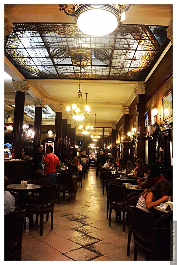 Внутри кафе: потолочные витражи, приглушенный свет, темного цвета панели, красивые колонны.