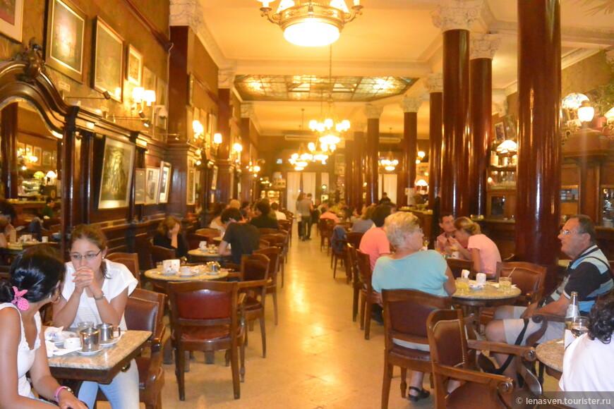 """В кафе """"Тортони"""" аншлага нет только утром, во время завтрака.  Внутри кафе - красивое и богатое убранство: панели темного цвета, в тон им - старинная мебель, витражи, лампы в стиле """"тиффани"""", желтоватый мрамор и бронза, также люстры в бронзе. В глубине зала - двустворчатые двери, которые ведут в другой зал, там - бильярдный стол и есть столики для игры в домино и кости."""