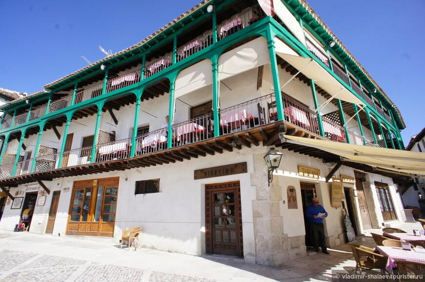 Все домики, выходящие на площадь, имеют схожую архитектуру. Окна и двери зданий выходят на деревянные галереи-балкончики, которые соединены между собой зелёными колоннами.