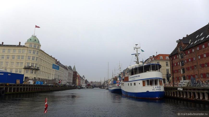 Параллельно домам идет такой же плотный ряд высоких мачт старинных кораблей, пришвартованных к набережной специально для создания аутентичной атмосферы