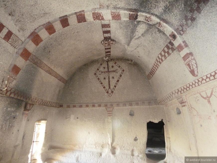 Айналы переводится с турецкого как Зеркальная. И действительно – древние строители (или правильнее – скалорубы) непонятно как, но сумели создать церковь абсолютно симметричную. Она имеет три нефа. В центральном нефе потолок сводчатый, в боковых – плоский. Здесь нет фресок на библейские сюжеты – только красные геометрические орнаменты на белом фоне известняковых стен, кресты и символические изображения животных.