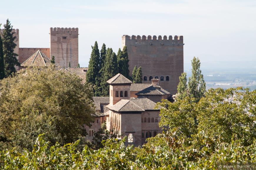 Небольшое здание по центру - Женская башня (или Девичья башня), далее постройки и башня Дворца Насридов, более высокие башни и стена между ними - крепость Алькасаба.