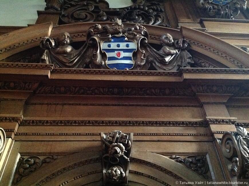Геральдика колледжа в окружении барочных деталей