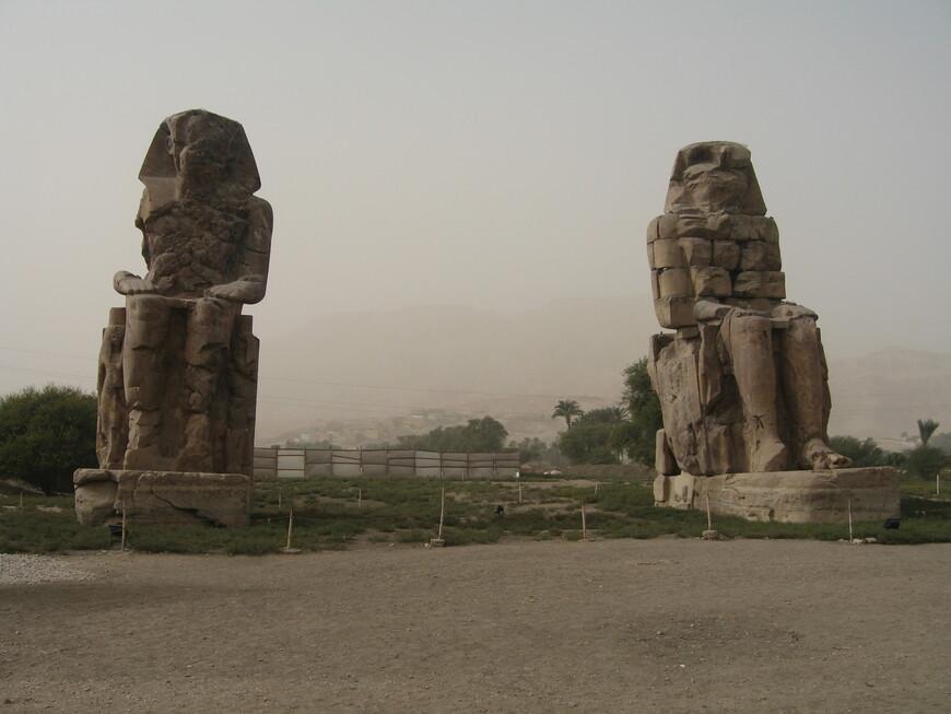 Колоссы Мемнона- это две статуи Аменхотепа  Третьего, которые были установлены  перед его поминальным храмом. Высота статуй 18 м , каждая весит 700 т. От поминального храма остались развалины, а статуи стоят уже 3400 лет