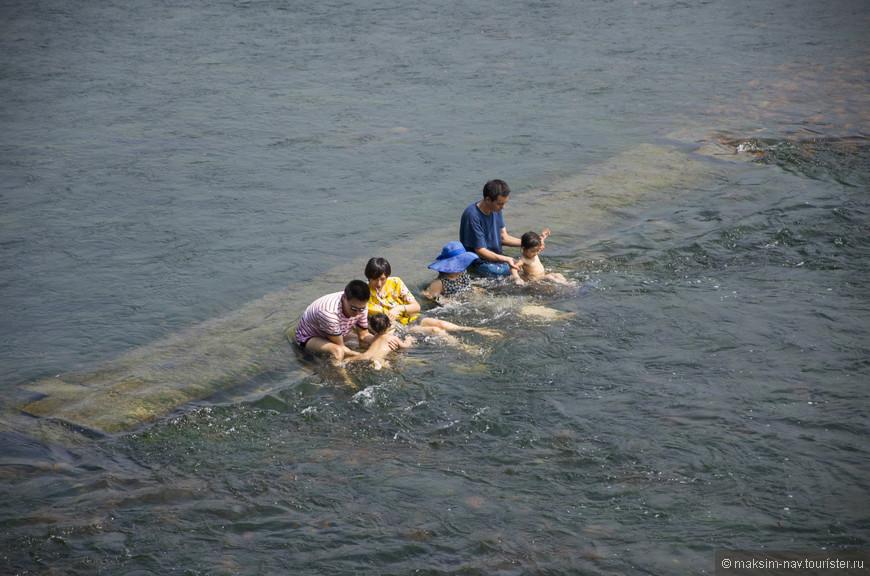 Китайцы релаксируют в реке целыми семьями – бесплатный гидромассаж.