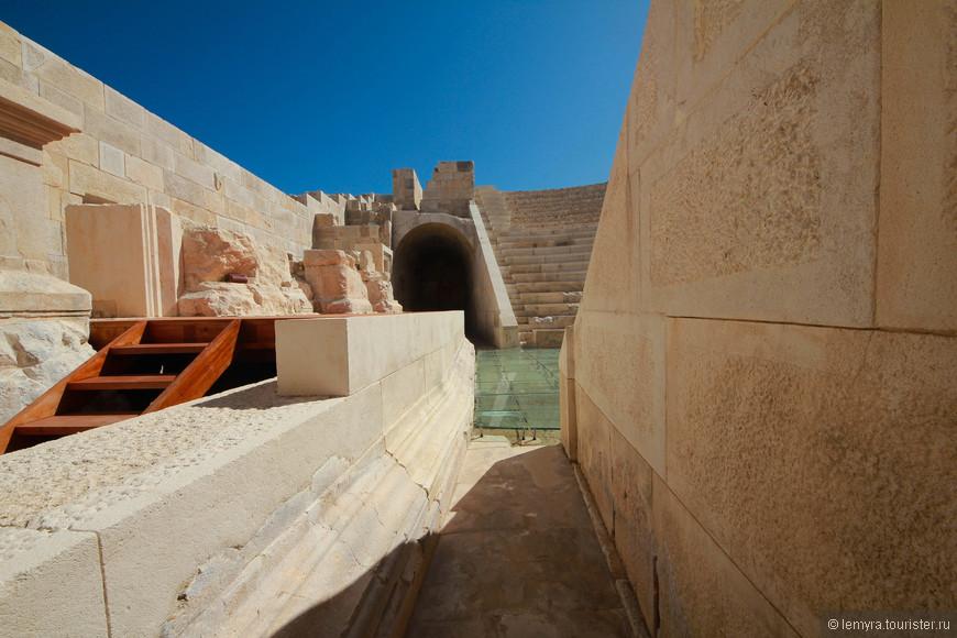 вход в театр, в результате раскопок от песка очистили ряды сидений. Также уцелело здание сцены с дверьми и арочными окнами.