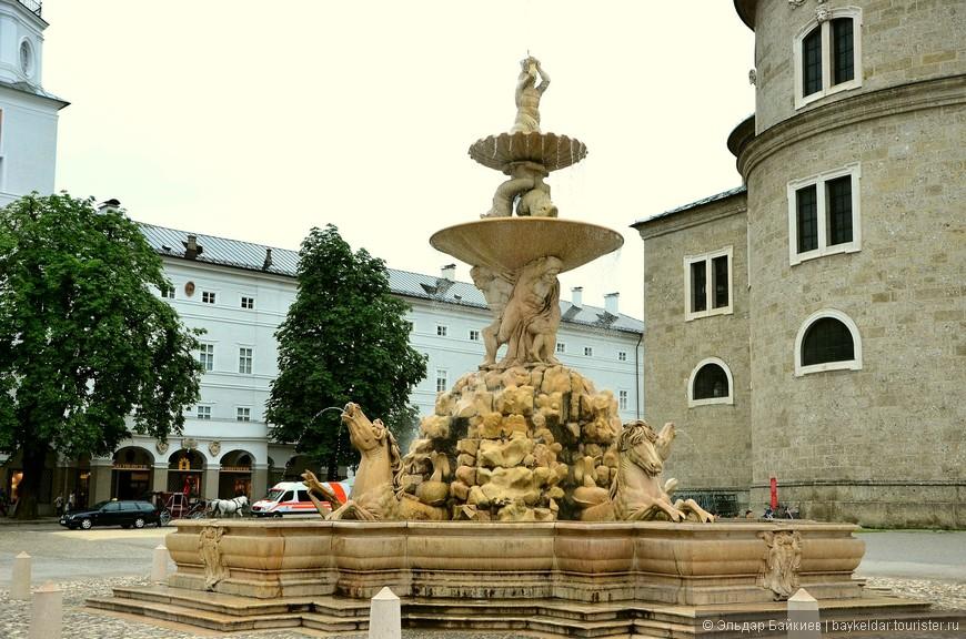 Главная площадь Зальцбурга расположена в сердце старой части города. В центре Резиденцплац установлен фонтан из мрамора в стиле барокко (Residenzbrunnen). Он является одной из главных достопримечательностей Зальцбурга. Фонтан на Резиденцплац считается самым красивым фонтаном в Зальцбурге. Он расположен между старой и новой резиденциями архиепископа. В основании фонтана бьют копытами лошади, из ноздрей которых вытекают тонкие струйки воды. Второй уровень фонтана представлен в виде огромной чаши, которую поддерживают четверо мужчин, а верхняя раковина располагается на хвостах дельфинов. Венчает конструкцию крупная фигура морского бога – из раковины над его головой в небо бьет мощный поток воды.  Площадь Резиденцплац была основана в 1587 году архиепископом фон Райтенау, который стремился освободить австрийский городок от узких средневековых улочек и подарить ему ощущение свободы и пространства.