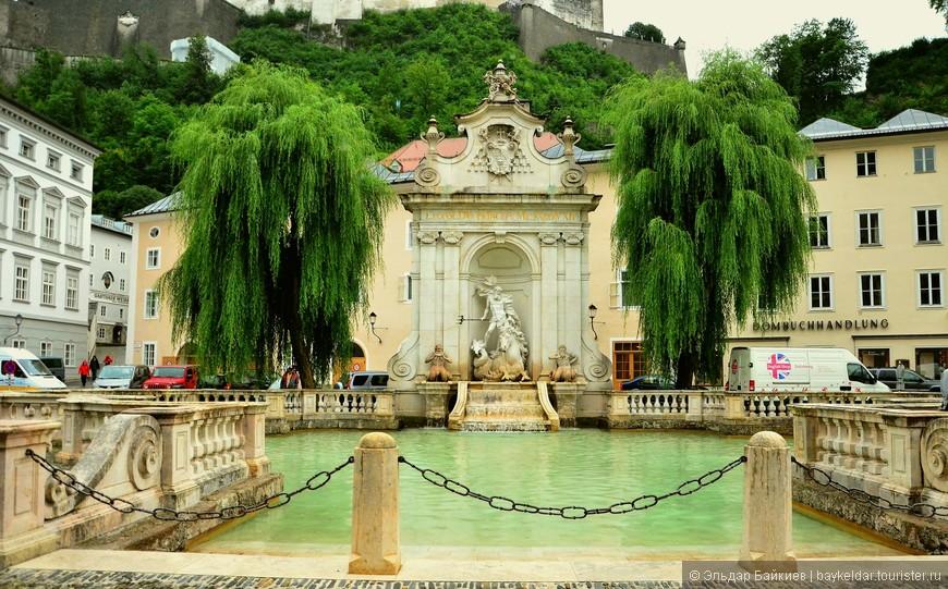 Фонтан «Нептун» - это огромная средневековая купальня для лошадей. Невероятно красивое архитектурное сооружение украшает площадь Kapitelplatz с 1732 года. Ранее здесь красовалась скульптура Пегаса. Теперь на ее месте в 18 веке возвели статую, которая возвеличивает морского Бога Нептуна. Сооружение, позволяющее подавать воду под давлением, создано каменщиком города Зальцбург Фафингером. Он выполнил свое творение в оригинальной форме – высокая стена с красиво оформленным изображением городского герба. Под стеной установлена статуя Нептуна, который сидит на своем морском коне. У ног морского правителя по ступенькам стекает вода в пруд.  Интересно, что над Нептуном на каменной стене золотыми буквами высечена надпись «Построен принцем Леопольдом». Каждая заглавная буква в латинском варианте надписи выгравирована в форме цифр, которые, если сложить вместе, указывают год создания фонтана. Это замечательное место считается стартовой точкой на пути к старинному замку в Зальцбурге.