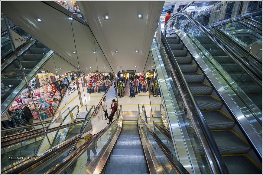 Спускаемся вниз. Кафешки обычно на верхних этажах. Ничего особенного тут нет. Вот только зря работающие эскалаторы удивляют, особенно, когда народу совсем не много. Трудно себе представить, чтобы я приехал в Сеул, чтобы здесь затовариваться. Хотя продают везде всего много и цены неплохие. Торговые площади - огромные, и порой складывается такое ощущение, что их с трудом заполняют товарами. Я сильно не копался в этом вопросе, но мне как-то сразу показалось, что в Таиланде шьют намного лучше...