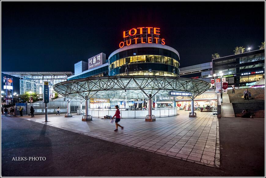 """Опускается ночной занавес и картина меняется. Привокзальная площадь ночью. Надпись Lotte, как я уже говорил, будет нас преследовать на протяжении всего путешествия. У них, похоже, все супер-универмаги так называются. Вот и на вокзале, похоже, тоже есть свой """"Лотте"""". Как удалось выяснить, Lotte Group - крупнейший южнокорейский конгломерат, основанный в Сеуле и объединяющий более 60 разных компаний. Это лидер розничного сектора, поэтому все, что связано с продажей, будет называться именно так."""