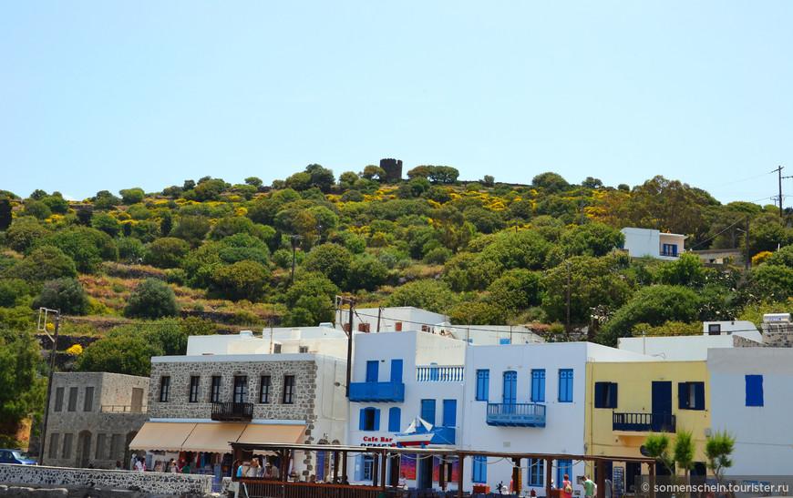 Над портом можно видеть античный акрополь и останки древнего города, окруженные крепостной стеной.