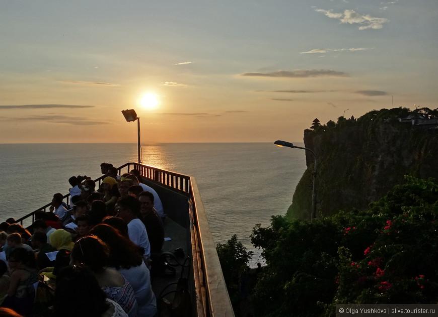 Ближе к закату все собираются в амфитеатре, откуда (если придти пораньше и забраться на самые верхние ряды) открывается шикарный вид на океан и на виднеющийся вдалеке храм Улувату...