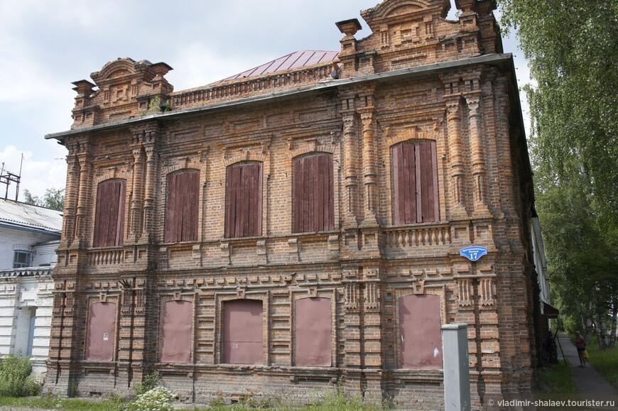 Старое кирпичное здание с деревянными ставнями и наглухо забитыми железом окнами первого этажа.