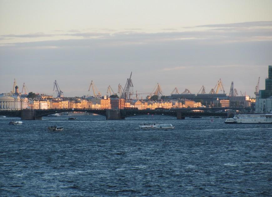 За Дворцовым мостом светится в лучах заходящего солнца Английская набережная, рядом с которой находятся Адмиралтейские верфи и порт. (Вид с Троицкого моста)