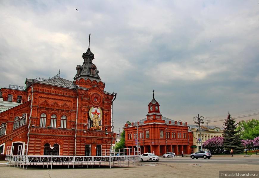 Здания городской Думы (слева) и здание Сбербанка на Соборной площади. Краснокирпичное здание городской Думы было выстроено в 1907 г., кроме Думы, вмещало ещё суд и страховую контору, а на первом этаже — и купеческие магазины