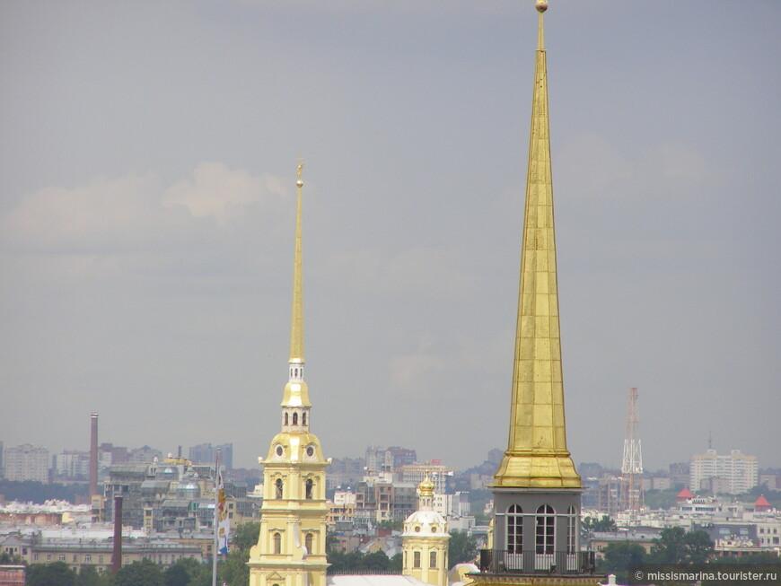 На фоне множества крыш зданий  выделяются  игла Адмиралтейства и шпиль Петропавловского собора.