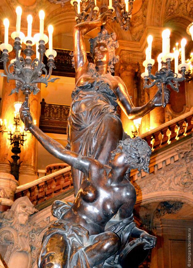 Внизу лестницы стоят два бронзовых торшера — женские фигуры, держащие букеты из света.