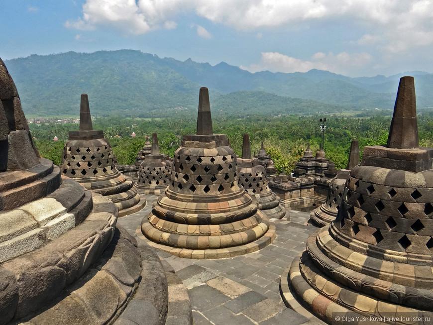 """Название Боробудура можно перевести как """"святилище на холме"""". Он воплощает собой буддийскую идею о восьми ступенях на пути к просветлению. Его цоколь символизирует мир плотских соблазнов. Следующие четыре яруса - борьбу с желаниями. А три круглые террасы без барельефов - последние этапы приобщения к нирване. Круглые ярусы украшены ступами (в форме колоколов), которые располагаются вокруг огромной центральной ступы высотой 7 м. Внутри малых ступ стоят статуи Будды."""
