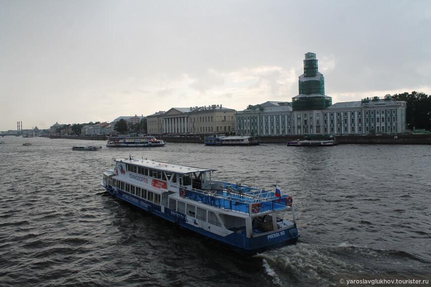 Накрапывает дождик, кораблик плывёт к пристани вдоль Университетской набережной Васильевского острова.