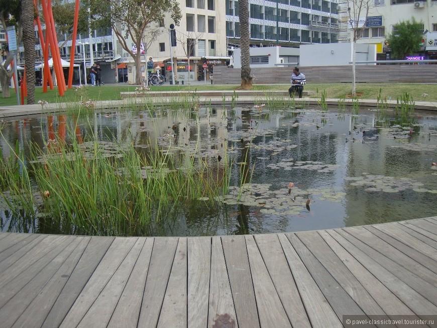 """Небольшой пруд на Кикар а-Ацмаут. На заднем плане - самый новый нетанийский отель """"Леонардо Плаза"""" (его открыли прошлой осенью, потому на фото видны отделочные работы)."""