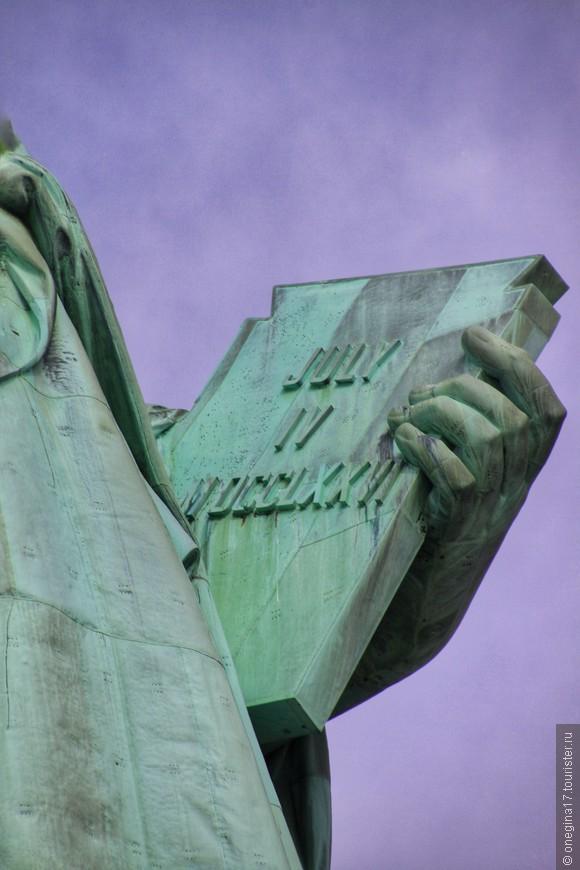 Понятно, что в руке Свобода держит Декларацию Независимости, на то она и свобода. Ну а даты, для сомневающихся - что же у нее там такое...
