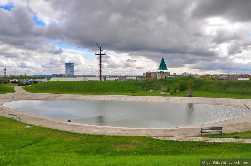 20. Искусственный водоем, насыпи по краям, сзади видна оборонительная башня. А совсем вдалеке – главное здание АвтоВАЗа.